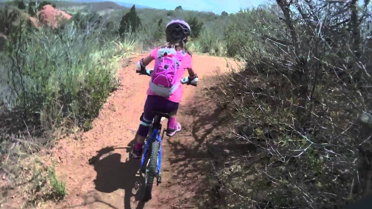 Young girl riding bike on trail